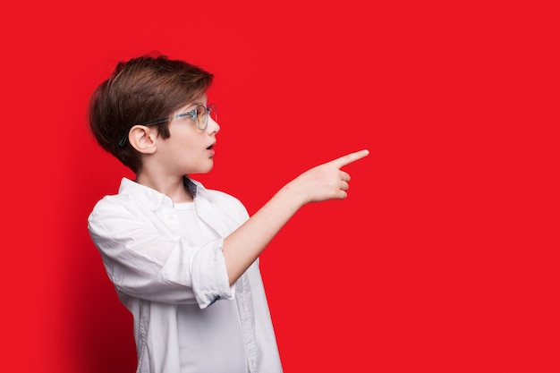 Menino caucasiano chocado com óculos e cabelo ruivo apontando para o espaço livre em uma parede vermelha