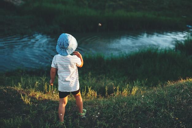 Menino caucasiano com chapéu azul jogando pedras no lago durante uma caminhada de verão