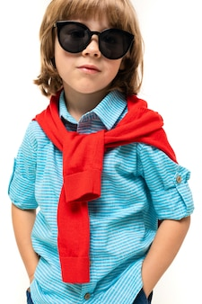 Menino caucasiano com sweatshot vermelho no pescoço e óculos de sol, isolados no fundo branco