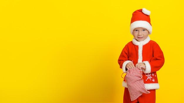 Menino caucasiano com uma fantasia festiva de papai noel e um saco aberto de presentes de ano novo
