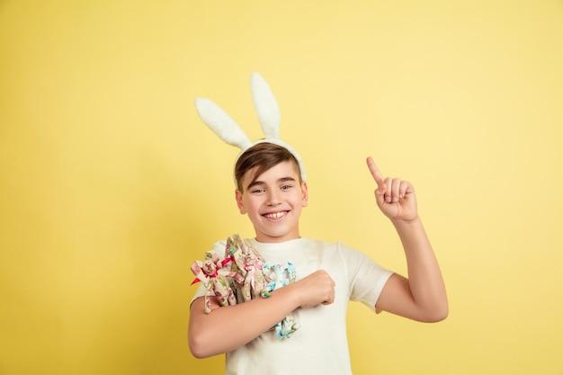 Menino caucasiano como um coelhinho da páscoa em fundo amarelo do estúdio.