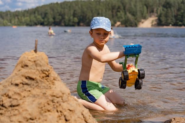 Menino caucasiano construindo um castelo de areia com um trator de brinquedo sentado na margem do lago da floresta