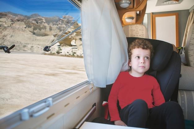 Menino caucasiano de cabelo encaracolado sentado perto da janela aberta de seu motorhome com uma vista espetacular