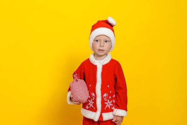 Menino caucasiano de três anos com uma fantasia festiva de papai noel segurando uma sacola com presentes