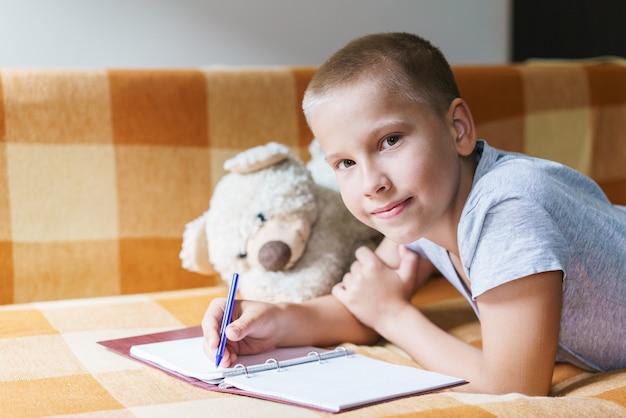 Menino caucasiano deitado no sofá faz sua lição de casa escreve com uma caneta em um caderno e sorri ao lado de oi ...