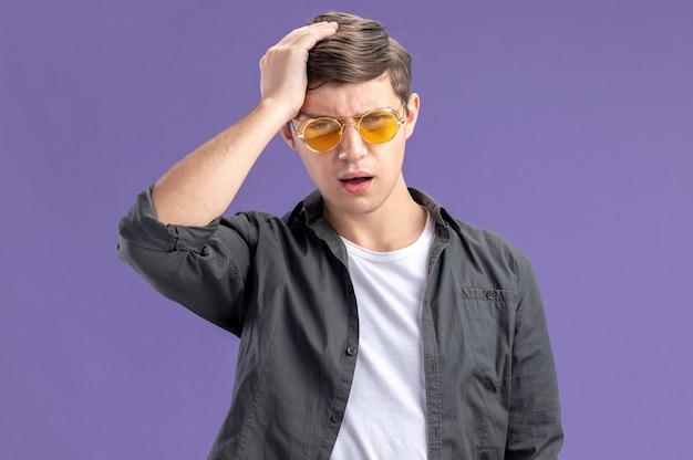 Menino caucasiano descontente com óculos de sol, colocando a mão na cabeça e olhando para a câmera