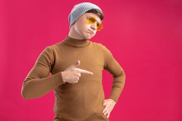 Menino caucasiano descontente com óculos de sol e chapéu de inverno apontando para o lado