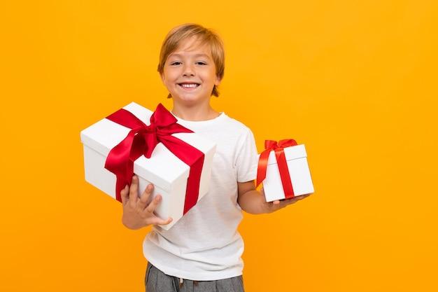 Menino caucasiano detém muitas caixas brancas com presentes e se alegra, retrato isolado na parede amarela