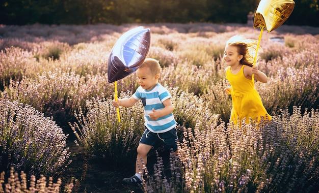 Menino caucasiano e sua irmã correndo em um campo de lavanda segurando balões estrela em um dia ensolarado