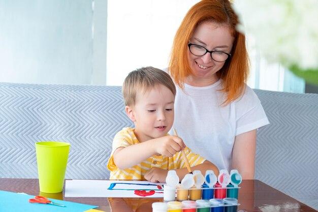 Menino caucasiano e uma jovem ruiva com óculos desenhados com tintas no papel