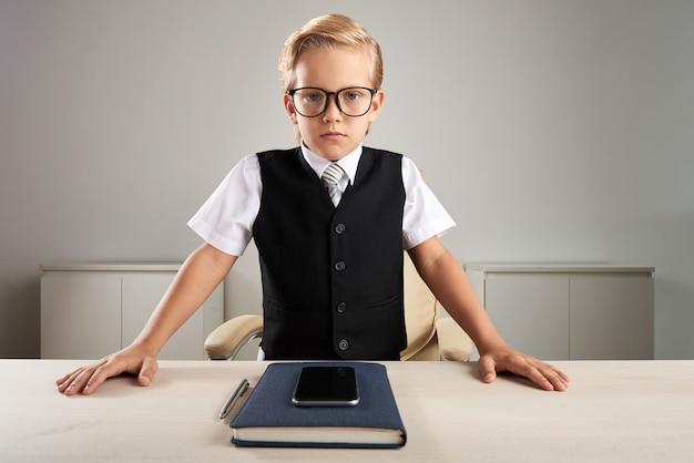 Menino caucasiano elegantemente vestido em pé atrás da mesa executiva no escritório