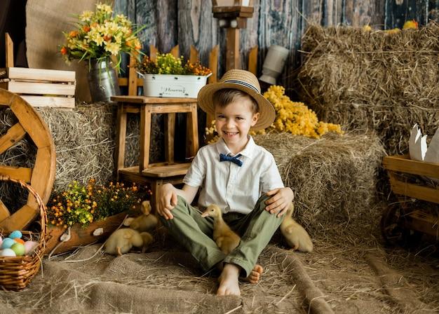 Menino caucasiano em uma camisa e calças. sentado com os patinhos na zona de páscoa. uma criança celebra a páscoa