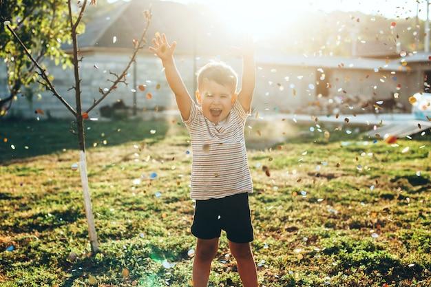 Menino caucasiano está brincando entre um monte de confetes voando perto dele no quintal de casa em um campo verde