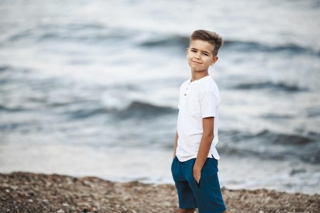 Menino caucasiano está de pé na praia, perto do mar ondulado, vestido com camiseta branca e calção azul