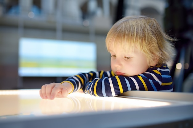 Menino caucasiano está procurando uma exposição em um museu científico