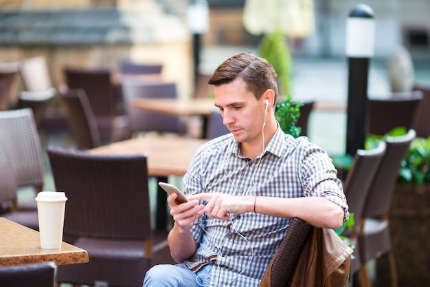 Menino caucasiano está segurando o celular ao ar livre na rua. homem usando smartphone móvel.