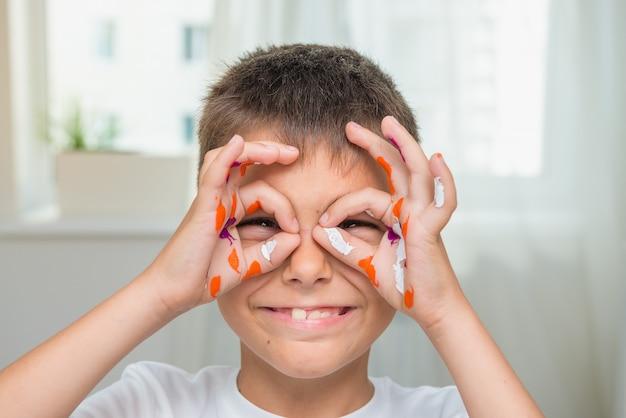Menino caucasiano feliz com mãos pintadas, artista alegre, foco seletivo.