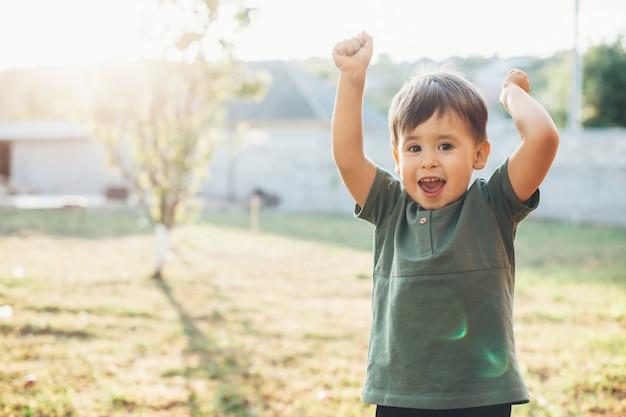 Menino caucasiano feliz gesticulando para uma vitória e comemorando o dia das crianças lá fora, no quintal, sorrindo para a câmera