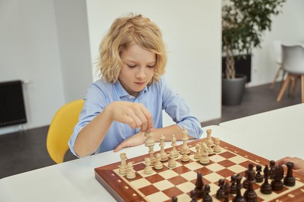 Menino caucasiano focado em uma camisa azul sentado na sala de aula e planejando sua jogada enquanto joga