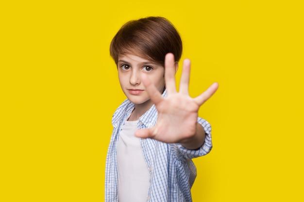 Menino caucasiano gesticulando com a palma da mão na placa de pare, posando na parede amarela do estúdio