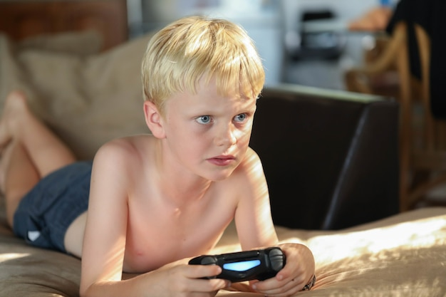 Menino caucasiano jogando videogame em casa no sofá na luz suave da tarde
