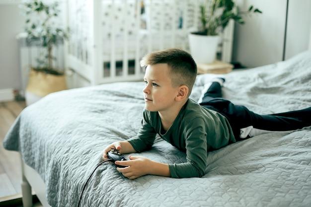 Menino caucasiano jogando videogame. estilo de vida, conceito de lazer.