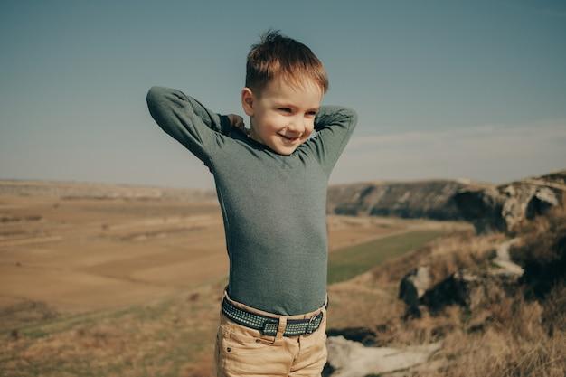 Menino caucasiano jovem na natureza, infância