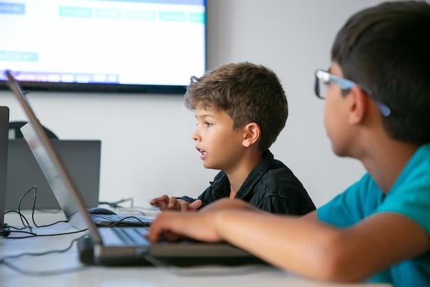 Menino caucasiano lendo tarefa em voz alta durante a aula