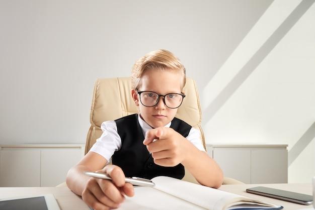 Menino caucasiano loiro de óculos, sentado na mesa no escritório e apontando em direção à câmera