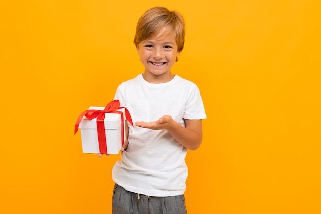 Menino caucasiano mantém caixa branca com presente e se alegra, retrato isolado na parede azul