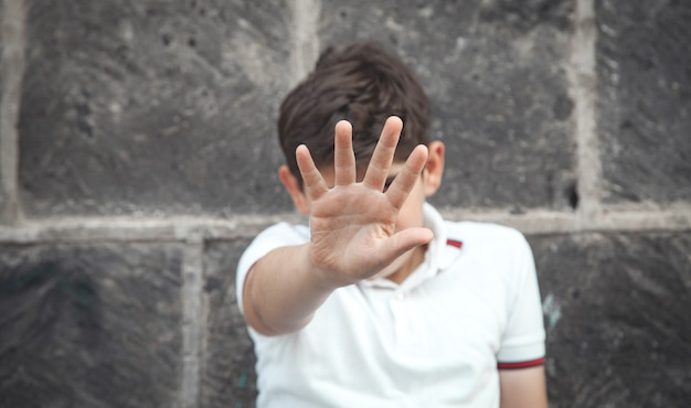 Menino caucasiano, mostrando o gesto de parada.