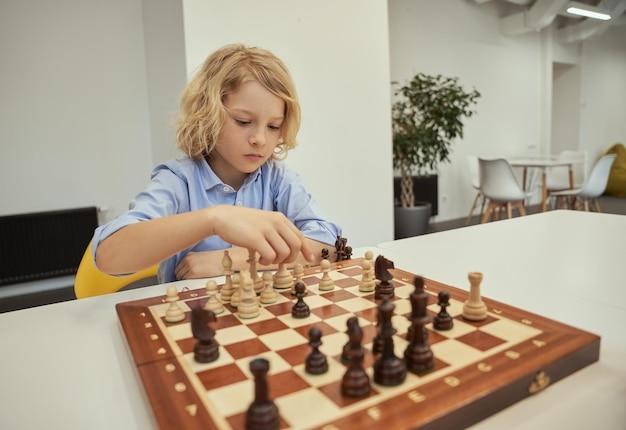 Menino caucasiano organizado, pensativo enquanto joga xadrez, sentado à mesa na escola