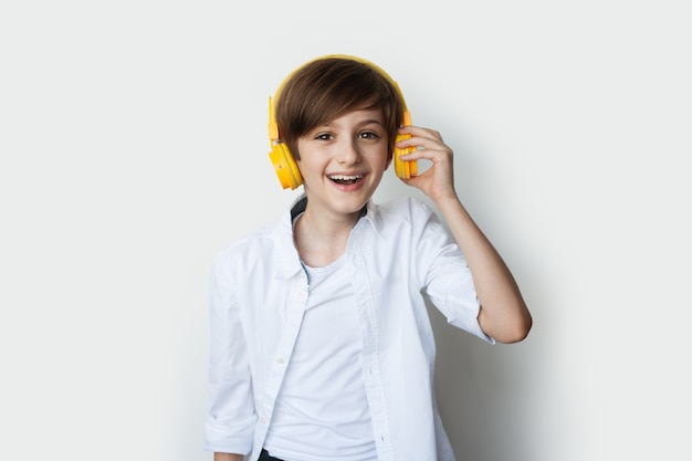 Menino caucasiano ouvindo música com fones de ouvido em um fundo branco