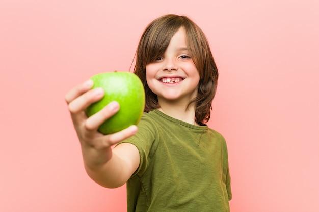 Menino caucasiano, segurando uma maçã