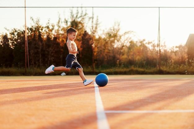Menino caucasiano sem camisa, correndo e chutando a bola na quadra de manhã no verão.