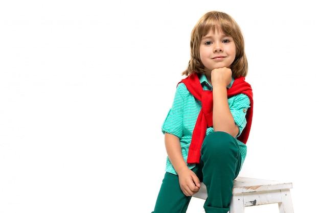 Menino caucasiano senta-se em uma cadeira com sweatshot vermelho em volta do pescoço, apoiado em um punho a cabeça isolada no fundo branco