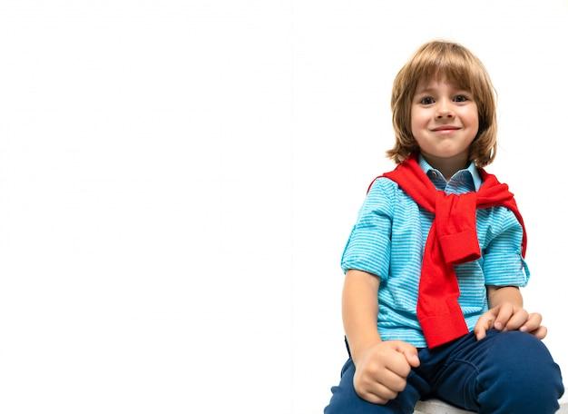 Menino caucasiano senta-se em uma cadeira com sweatshot vermelho no pescoço, isolado no fundo branco