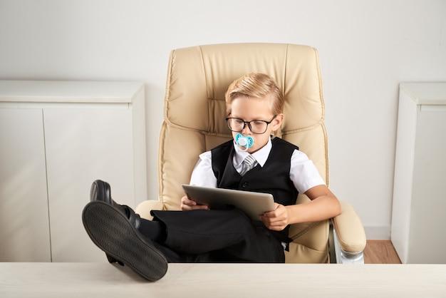 Menino caucasiano, sentado na cadeira executiva no escritório com boneco na boca e usando tablet
