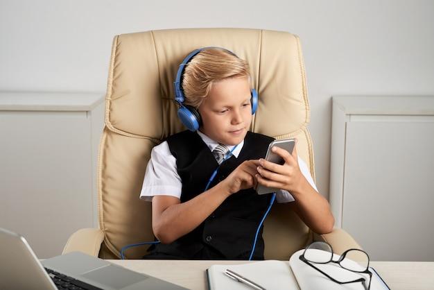 Menino caucasiano, sentado na mesa executiva no escritório, com fones de ouvido e smartphone