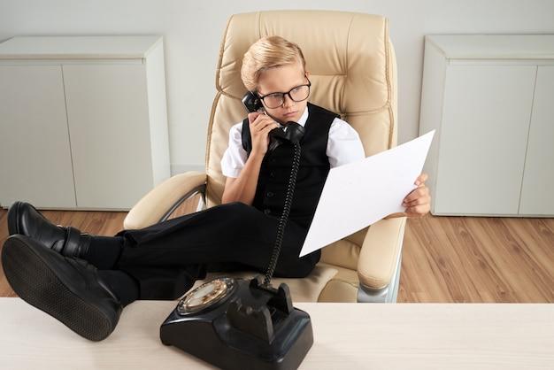 Menino caucasiano, sentado no escritório, na cadeira executiva, com os pés na mesa e falando no telefone