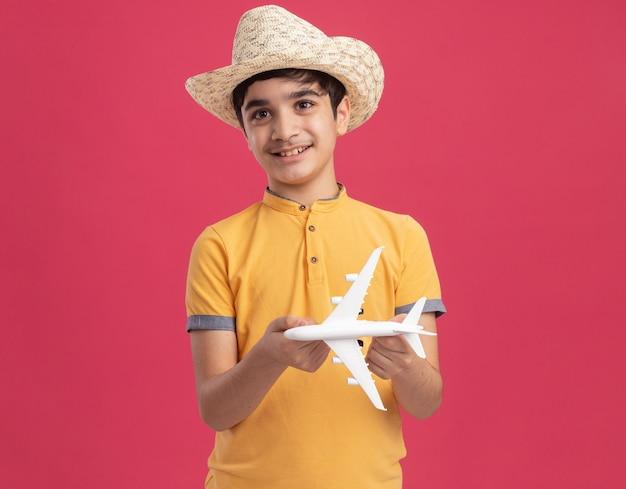 Menino caucasiano sorridente com chapéu de praia segurando modelo de avião olhando direto