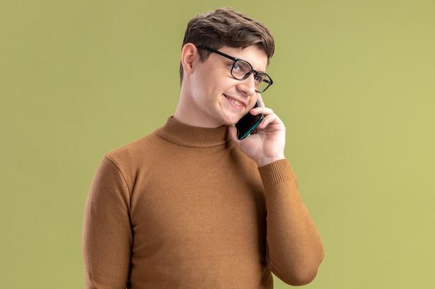 Menino caucasiano sorridente com óculos ópticos falando no telefone e olhando para o lado