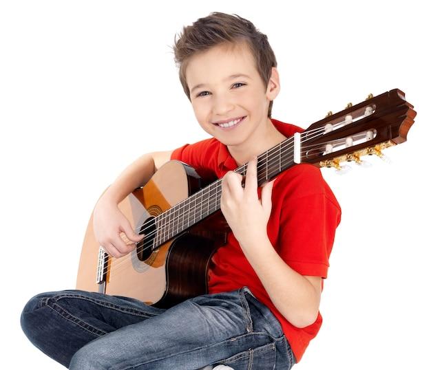 Menino caucasiano sorridente está tocando violão -