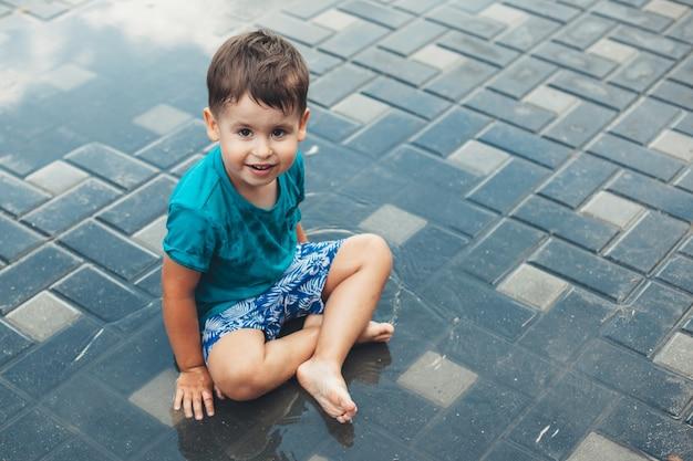 Menino caucasiano sorridente, olhando para a câmera e sorrindo enquanto brinca na água no chão