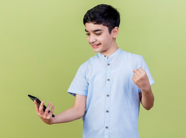 Menino caucasiano sorridente segurando e olhando para o celular, fazendo gesto de sim isolado em fundo verde oliva