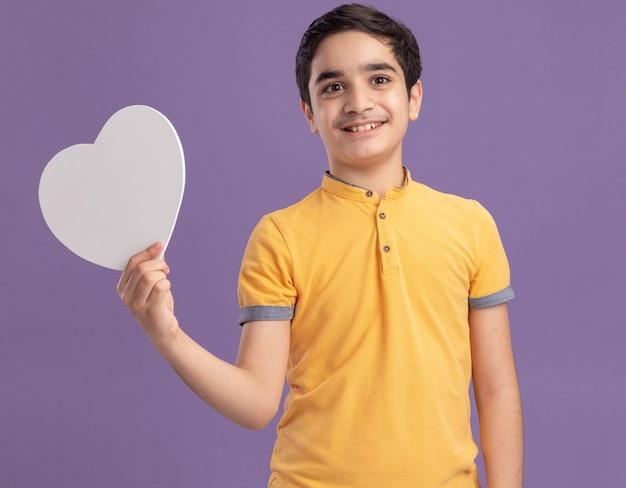 Menino caucasiano sorridente segurando um formato de coração olhando para o lado