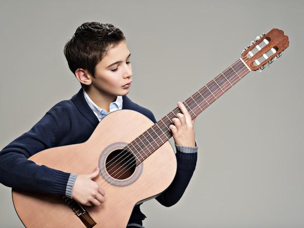 Menino caucasiano tocando violão.
