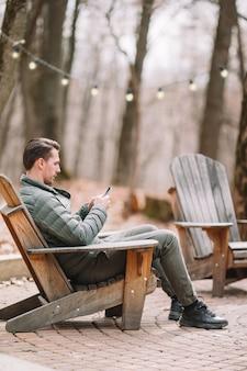 Menino caucasiano turista com celular ao ar livre no café. homem usando smartphone móvel.
