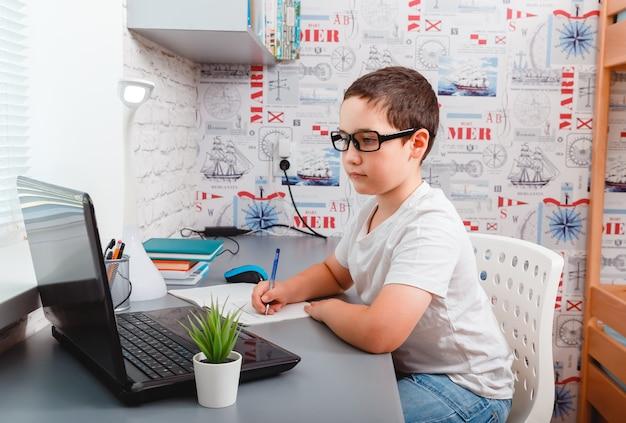 Menino caucasiano usando computador desktop para estudo on-line em casa
