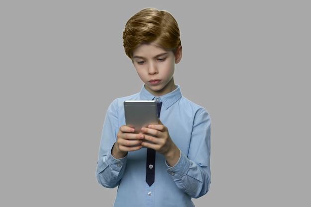 Menino caucasiano usando smartphone em fundo cinza. criança brincando no smartphone. tecnologia, aplicativos móveis, crianças e conceito de estilo de vida.